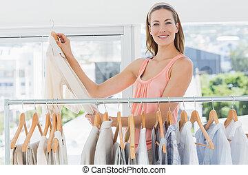 mooi, vrouwlijk, manierontwerper, met, rek, van, kleren, in, winkel