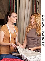 mooie meisjes, het selecteren, textiel, en, het glimlachen., blonde , staande vrouw, in, winkel, en, het glimlachen