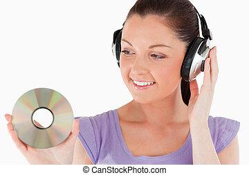 mooie vrouw, met, headphones, vasthouden, een, cd, terwijl,...