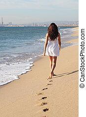 mooie vrouw, wandelende, op het strand