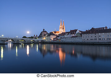 Moon above Regensburg in the evening with view to the Cathedral and stone bridge, Germany