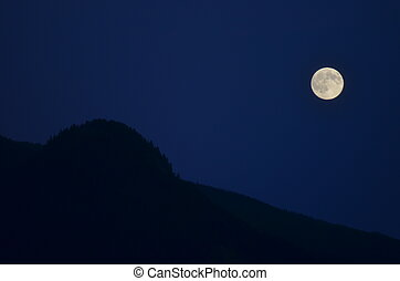 The moon over a mountain silhouette