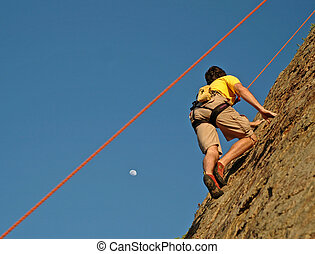 Climber climbs up California Cliff at Sunset and moon rise