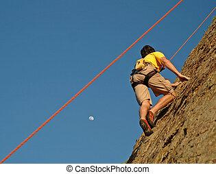 Moon Climb - Climber climbs up California Cliff at Sunset...