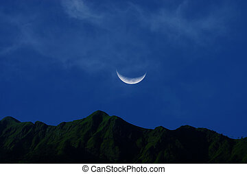 Moon crescent in the blue sky.