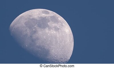 Moon crosses the blue sky - Closeup of moon crossing the ...