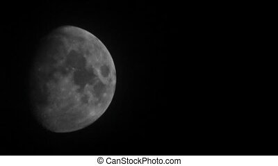 Moon crossing night sky behind scarce clouds. Telephoto lens...