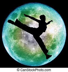 Moon dance - Young woman jumping silhouette against the moon
