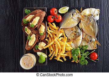 moon fish, chips, beer and toasts on slate tray