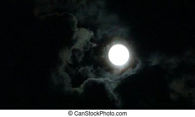 Moon glows through the dark night clouds