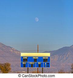 Moon hangs above the scoreboard of baseball field