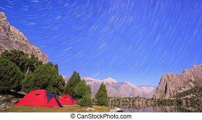 Moon illuminates the mountains. Traces of stars similar to metory. TimeLapse. Pamir, Tajikistan