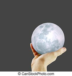A hand holding a softly glowing moon against a black background