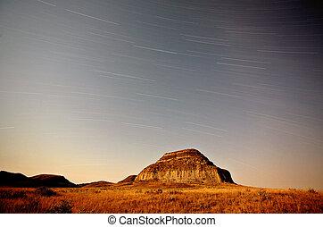 Moon lit Castle Butte and star tracks in scenic Saskatchewan