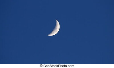 Moon movement in evening blue sky
