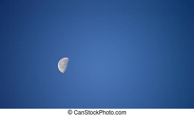 Moon moves across cloudless blue sky