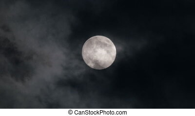 moon moving between clouds