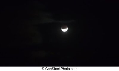 Moon moving on night sky during partial eclipse - Moon...