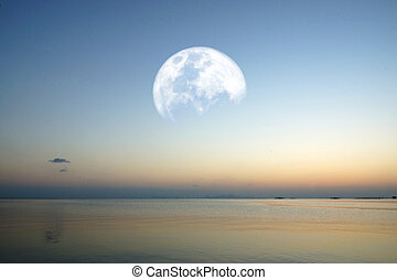 moon on lake with blue sky and colorful sunset