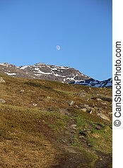 Moon over mountains and grassland at valley Karkevagge in Northern Sweden