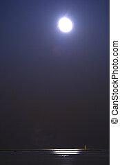 Moon over quiet water - A full moon hangs over a flat ocean...