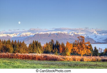 Moon rising over the Kenai mountains with fall colors and warm evening light.