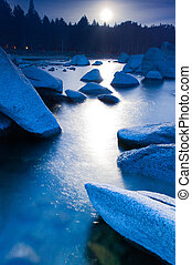 Moon rise over boulders in Lake Tahoe - The moon reflects on...