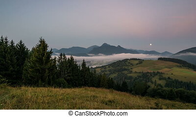 Moon set dawn and sunrise in foggy mountains landscape Time...