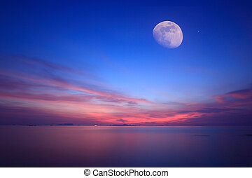 Moonlight over blue sea and fire sky ,Long exposure...