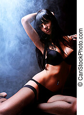 moonlight - Shot of a sexy woman in black lingerie over dark...