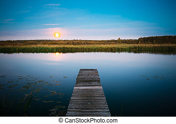 Moonrise over river lake pond in summer evening. Wooden boards pier