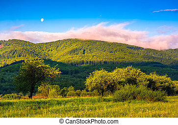 moonrise over the mountain in rural area at sunset -...