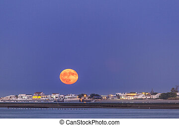 Moonrise seascape at Ria Formosa conservation wetlands,...