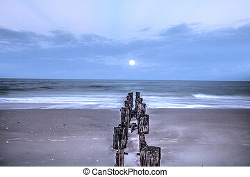 Moonset at Dawn over a dilapidated pier on the beach in Port Royal