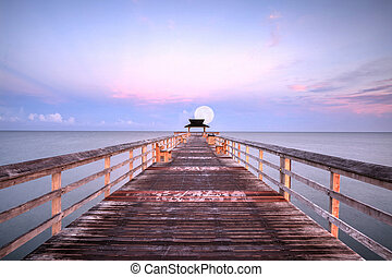 Moonset at Early sunrise over the Naples Pier on the Gulf Coast of Naples, Florida