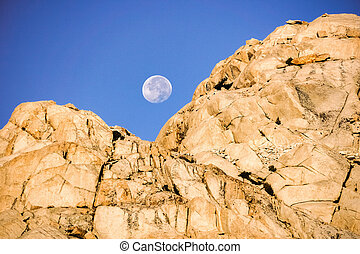 Moonset behind a rocky mountain at sunrise, Eastern Sierra Mountains, Mount Whitney Trail, California