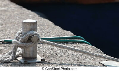 Moored boat - Detail of a rope tied up to bitt of a jetty