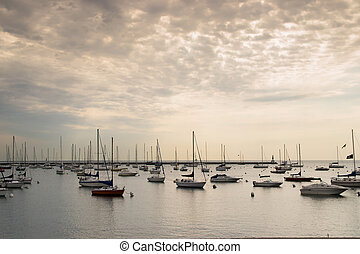 boats are moored in chicago pier at sunset
