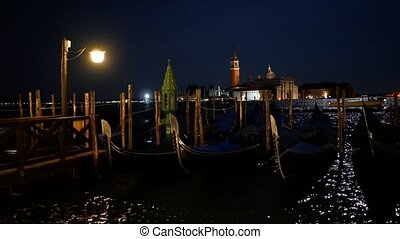 Moored gondolas in Venice at night and distant San Giorgio...