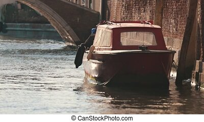 Moored launch floating under the bridge. Italy. Close up