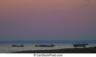 Moored motor boats rocking on sea waves in the dusk