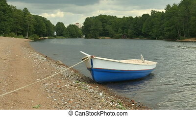 Moored Rowing boat with oars on the river bank