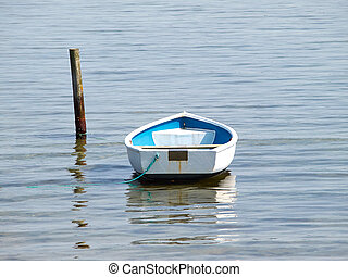 Moored small dingy rowing boat on still calm water