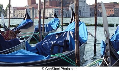 Moored Venetian gondolas swaying against cityscape. Venice,...