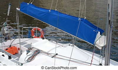 Moored yacht with a blue sail
