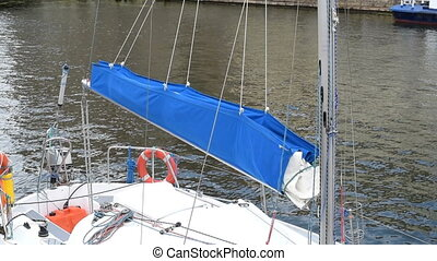 Moored yacht with a blue sail - Moored yacht. Moored boat at...