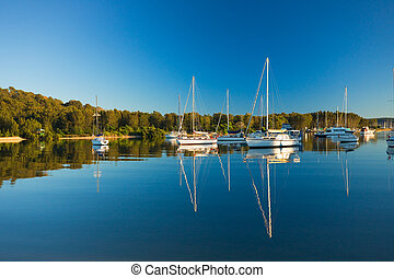 Moored yachts reflected against blue sky - Moored yachts sit...