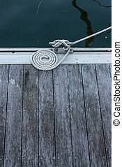 Mooring bollard with cord on a wooden pier