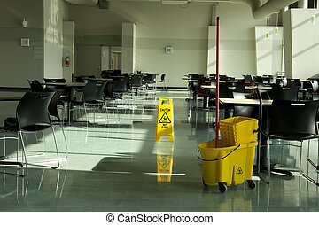 mop bucket caution sign cafe tables - A mop, bucket and...