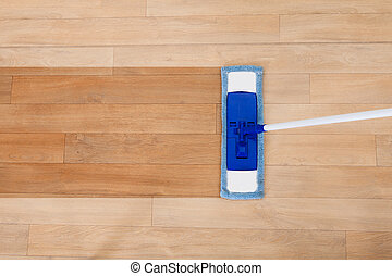 Mop cleaning a wooden floor - Overhead view of a modern...